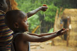 A Bassari Child Holding Out Hands to Collect Rainwater  Bassari Country  East Senegal
