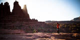 A Male Hiker Enjoys the Rising Sun's Warmth at Fisher Towers in Moab  Utah