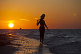 A Silhouette of a Woman Wearing a Hat Walking in the Surf at Sunset on Holbox Island  Mexico