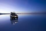 Travelers Drive their Suv across a the Salar De Uyuni  a Flooded Salt Flat  in Bolivia