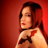 Photo of Beautiful Sexy Girl with Bat Tattoo on Shoulder Isolated on Red Background  Halloween Holi