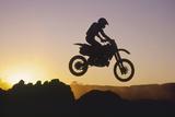 Motocross Rider in Silhouette against Sunset Sky