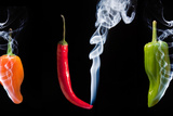 Red Green and Orange Hot Chilli Peppers with Smoke Coming out of Tips