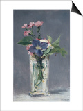 Oeillets et clématites dans un vase de cristal
