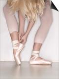 Ballerina adjusting toe shoe