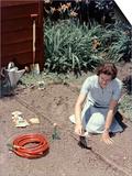 1950s Woman Kneeling in Garden Planting Seeds in Soil