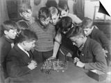 Two Boys Sit for a Game of Chess Eight Spectators Look On