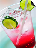 A Glass of Raspberry Soda with Ice Cubes and Lime Slices