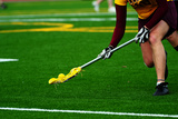 Lacrosse Player Scooping up the Ball on a Turf Field