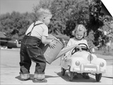 1950s Little Boy Playing Gas Station Pouring Water into Toy Car for Little Girl