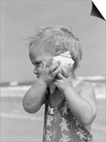 1950s Blond Toddler Girl Listening to Ocean in a Seashell Wearing Teddy Bear Bathing Suit