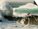 Surf Crashing near Surfer on Boulders