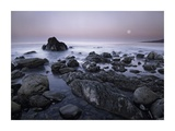 Full moon over boulders at El Pescador State Beach  Malibu  California