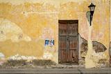 Broken Plaster on Yellow Wall with Old Wood Door