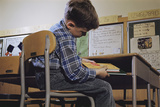 Schoolchild Placing Books in Desk