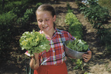 Girl Holding Head of Lettuce in Garden