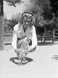 Woman Kneels and Pets Baby Ostrich