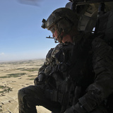 A US Army Special Forces Soldier Looks Out from a Uh-60 Black Hawk