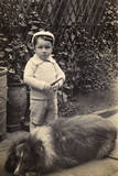 Little Boy with Large Dog in a Garden