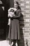 Woman with Pekingese Dog Outside a House