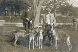 Two Men with Five Dogs in a Garden