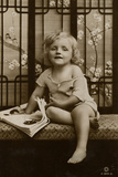 Little Girl Sitting on a Bench with Picture Book