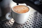White Ceramic Cup of Fresh Espresso with Foam in the Coffee Machine