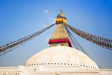 Bodhnath Stupa with Buddha Eyes and Prayer Flags  Clear Blue Sky  Kathmandu  Nepal Stock Photo: