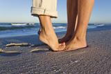 Feet of Couple Hugging on Beach