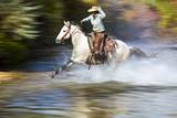 Cowgirl Riding through River on Horse