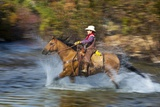 Young Cowboy Crossing River on His Horse
