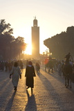 View Towards the Koutoubia Minaret at Sunset with Local People Walking Through the Scene