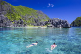 Tourists Swimming in the Crystal Clear Water in the Bacuit Archipelago  Palawan  Philippines