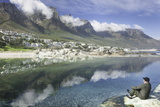 Man Sits on Rock Facing Twelve Apostles Mountain Reflected in Atlantic Ocean  Camp's Bay  Cape Town