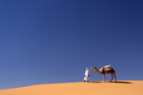 Berber Man with Camel on the Ridge of an Orange Sand Dune in the Erg Chebbi Sand Sea