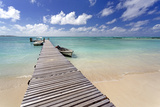Wooden Jetty with Boats Tied to it Stretching Out into the Indian Ocean Off an Idyllic Beach
