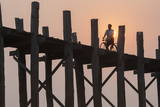 Man on Bicycle Silhouetted at Sunrise Crossing Taungthaman Lake on U Bein Teak Bridge at Dawn