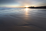 View over Embleton Beach at Sunrise Towards the Silhouetted Ruin of Dunstanburgh Castle