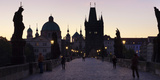 Silhouette of Statues on Charles Bridge with St Francis Church and Old Town Bridge Tower