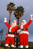 Two Santas Waving under Palm Trees in California