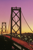 This Is the Bay Bridge at Sunset There Is a Pink and Orange Glow in the Sky