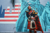 A Man in Kilt Playing Bagpipes in Front of a Patriotic Mural  St Patrick's Day Parade  Ny City