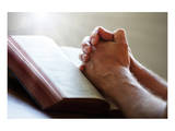 Hands Praying on a Holy Bible