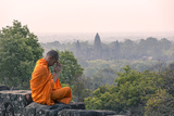 Cambodia  Siem Reap  Angkor Wat Complex Monk Meditating with Angor Wat Temple in the Background
