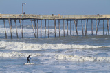 A Boy Paddles Out into Big Waves on His Standup Paddle Board Next to Nags Head Pier