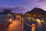 Warmly Lit Over-The-Water Bungalows at a Tropical Resort at Dusky