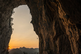 A Climber Descends the Great Arch of Chuanzhang Cave at Sunset