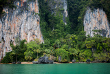 Limestone Cliffs Loom over a Remote Beach and Palm Trees in Thailand
