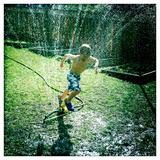 A Seven Year Old Boy Runs Through a Back Yard Sprinkler