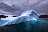 A Shimmering Blue Iceberg in a Bay Off Unartoq Island  under a Cloudy Brooding Sky